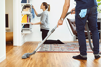 Low section of man vacuuming floor while woman cleaning shelves in background at home - p426m1151747 by Maskot
