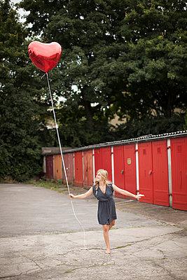 Woman holding balloon - p586m859536 by Kniel Synnatzschke