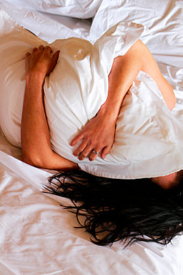 Woman clutching pillow on bed - p967m892222 by Wessel Wessels