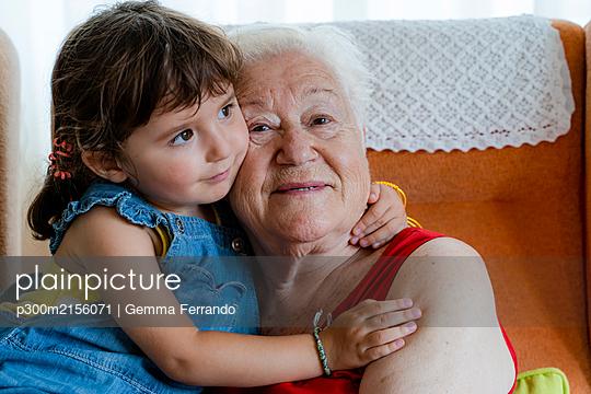 Smiling grandmother hugging her granddaughter at home - p300m2156071 by Gemma Ferrando