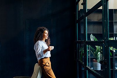 Young businesswoman looking out of window in loft office - p300m2144469 by Sofie Delauw
