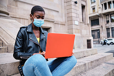 Young woman wearing protective face mask using laptop while sitting on steps in city - p300m2250189 by Alvaro Gonzalez