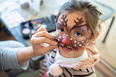 Cute girl with painted face at home during Christmas - p300m2266327 by Ignacio Ferrándiz Roig
