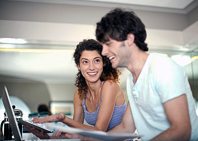 Young man and woman (22-25) looking at laptop and iPad and paperwork in the kitchen, Cape Town, South Africa - p300m2293238 von LOUIS CHRISTIAN