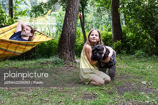 Mädchen kuschelt mit ihrem Hund - p294m2206263 von Paolo
