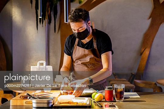 Male expertise with protective face mask keeping burger in serving tray at restaurant - p300m2274281 by Javier De La Torre Sebastian