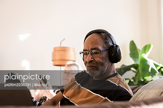 Senior man with headphones using laptop at home - p426m2238231 by Maskot