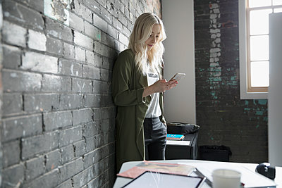 Creative businesswoman texting with smart phone along brick wall in office - p1192m1447459 by Hero Images
