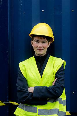 Junge Frau mit Schutzhelm vor Container - p1212m1123181 von harry + lidy