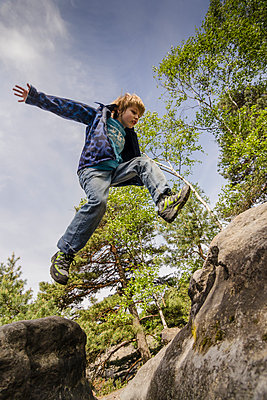 Germany, Saxony, Saxon Switzerland, Lilienstein, Young boy jumping over stones - p300m965252f by Andreas Pacek