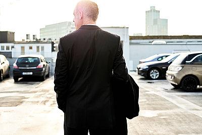 Geschäftsmann auf einem Parkdeck - p890m1217278 von Mielek