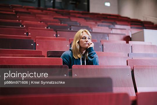 Blonde Studentin sitzt nachdenklich im Hörsaal - p586m971606 von Kniel Synnatzschke