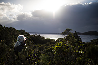 Woman in nature looking at the sun and the sea - p1007m1540393 by Tilby Vattard