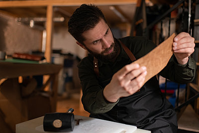 Male artisan inspecting piece of leather - p1166m2234386 by Cavan Images