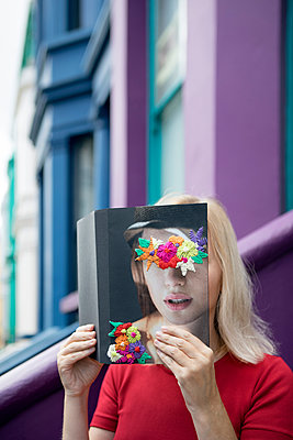 Woman covering face with book, reading poetry - p300m1581382 von Petra Stockhausen