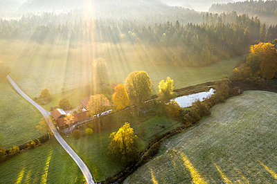 Germany, Bavaria, Aerial view of Kirchseebach river and Pelletsmuehl, sun light and morning fog - p300m2070767 by Martin Siepmann
