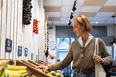 Woman checking fruit kept in retail display at supermarket - p300m2286897 by NOVELLIMAGE