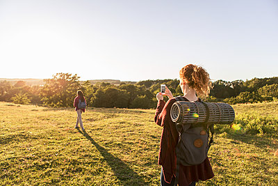 Rear view of woman photographing daughter standing on field against sky during sunset - p426m1588236 by Kentaroo Tryman