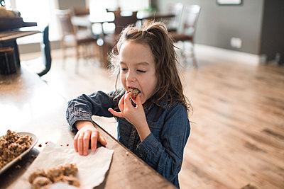Little girl eating freshly baked vegetarian seed ball - p924m2074178 by Viara Mileva