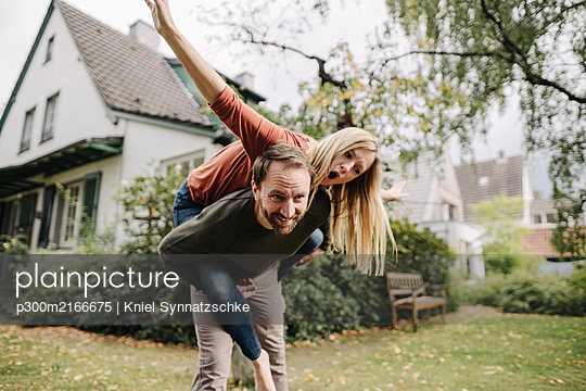 Cheering couple pretending to fly, standing in their garden - p300m2166675 by Kniel Synnatzschke