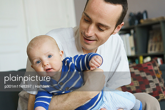 Close-up of father playing with son at home - p301m1148397 by Halfdark