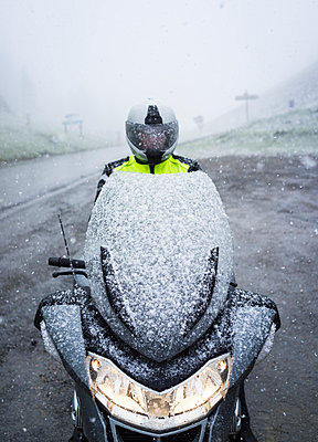 Snow covered motorcyclist sitting on motorcycle - p1053m793974 by Joern Rynio