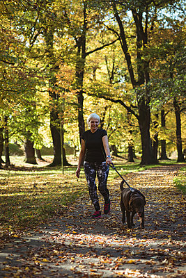 Senior woman walking in the park with her pet dog on a sunny day - p1315m1565683 by Wavebreak
