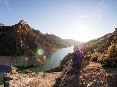 Spain, Gueejar Sierra, back view of hiker looking at Genil River at evening sunlight - p300m1460182 by Albrecht Weisser