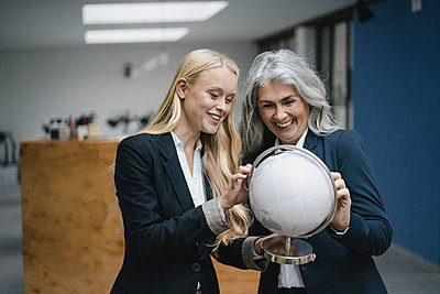 Happy mature and young businesswoman looking at globe - p300m2171021 by Gustafsson
