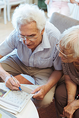 High angle view of senior couple doing crossword puzzle in newspaper at nursing home - p426m2072598 by Kentaroo Tryman