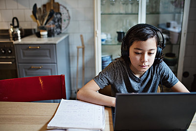 Boy wearing headphones while using laptop during homework at home - p426m2101747 by Maskot