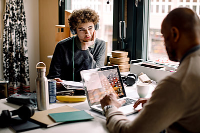 Teenage boy looking at male entrepreneur working while sitting at desk - p426m2279681 by Maskot