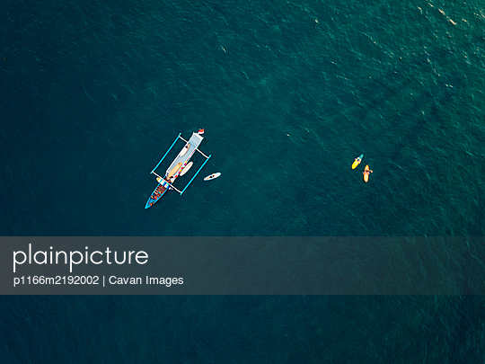 Aerial view of surfers and boat in the ocean, Lombok, Indonesia - p1166m2192002 by Cavan Images