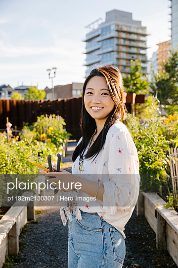 Portrait happy young woman with smart phone in sunny, urban community garden - p1192m2130307 by Hero Images