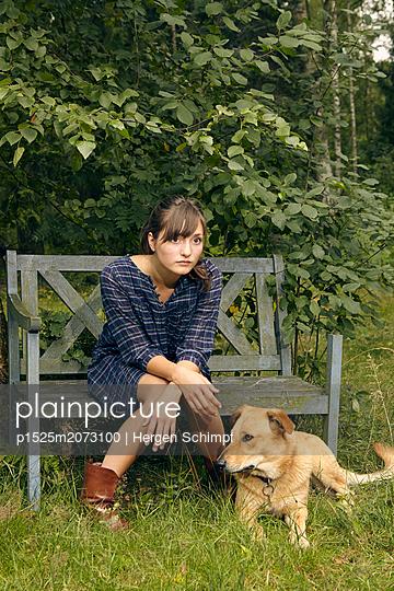 Junge Frau auf einer Gartenbank - p1525m2073100 von Hergen Schimpf