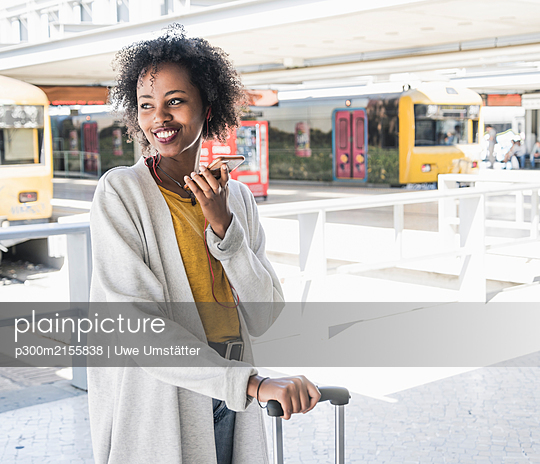 Happy young woman with earphones using smartphone at station platform - p300m2155838 by Uwe Umstätter