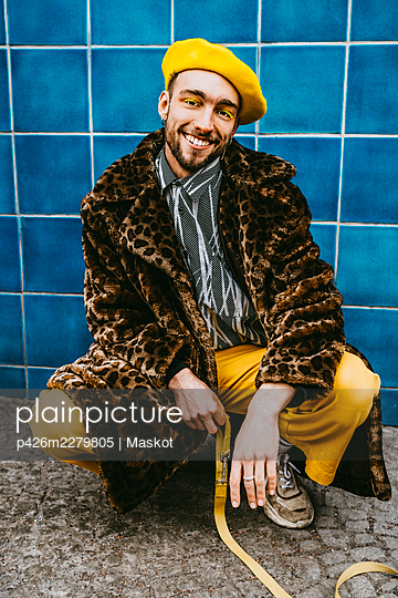 Full length of young man wearing coat crouching against blue tiled wall - p426m2279805 by Maskot