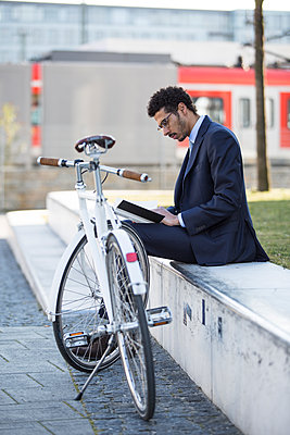 Businessman with bicycle taking a break in city - p1026m1139959 by Patrick Frost