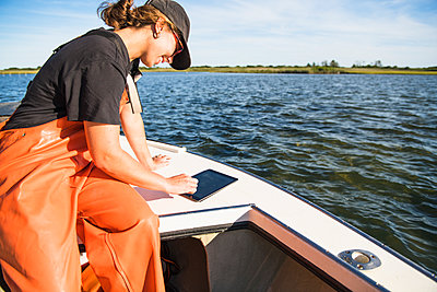 Woman with tablet working on the water in aquaculture oyster farm - p1166m2268902 by Cavan Images