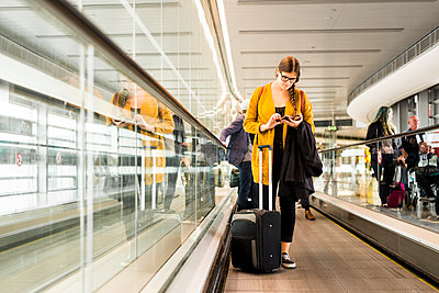 Businesswoman using smart phone on moving walkway in airport - p1264m1122099f by Astrakan