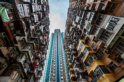 Hong Kong, Quarry Bay, apartment blocks contrasting with modern skyscraper - p300m2069707 by Daniel Waschnig Photography