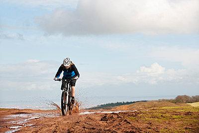 Woman riding mountain bike through mud - p42911560f by Colin Hawkins