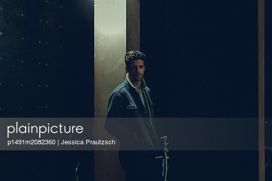 Mann steht in dunklem Kellerraum - p1491m2082360 von Jessica Prautzsch