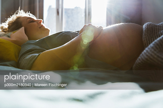 Pregnant woman lying on bed at home - p300m2180940 by Mareen Fischinger