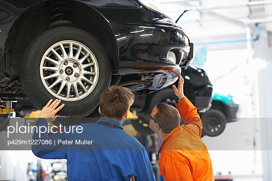 Rear view of college mechanic students inspecting  underneath of car - p429m1227086 by Peter Muller