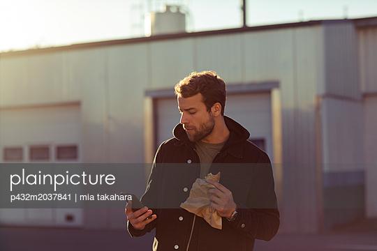 Mann blickt auf sein Handy - p432m2037841 von mia takahara