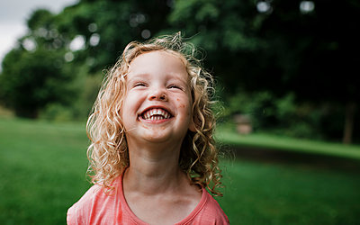 Cute cheerful girl looking away at park - p1166m2024982 by Cavan Images