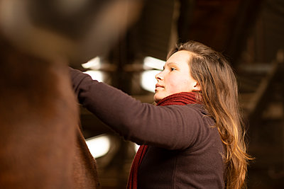 young woman with a horse in a horse stable - p1166m2148589 by Cavan Images