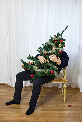 Man hugging a decorated Christmas tree - p1621m2231158 by Anke Doerschlen