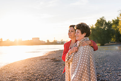 Happy senior woman standing with her adult daughter on the beach at sunset - p300m1459818 by Uwe Umstätter